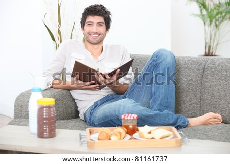 Man sitting on a sofa eating breakfast and reading a book - stock photo
