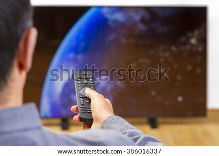 Man sitting on a sofa watching tv holding remote control. Focus on the remote control. - stock photo
