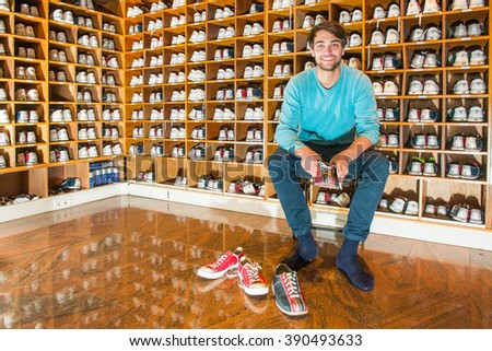 Man, sitting on a stool, surrounded by wooden shelves with various sizes of bowling shoes, trying on the sports wear, ready to go bowling - stock photo