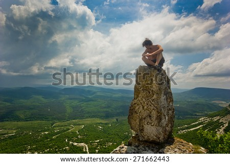 man sitting on a top of stone in mountains with clouds on sky and forest below - stock photo