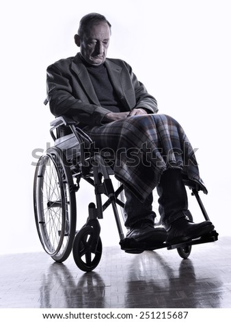 Man sitting on a wheelchair looking down - stock photo