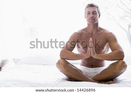 Man sitting on bed meditating - stock photo