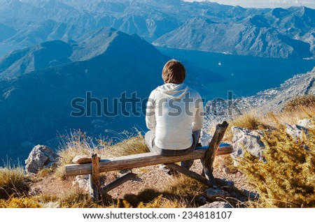 Man sitting on bench, high up in the mountains enjoying Beauty world, looking from Lovcen mountain in Kotor, Montenegro. - stock photo