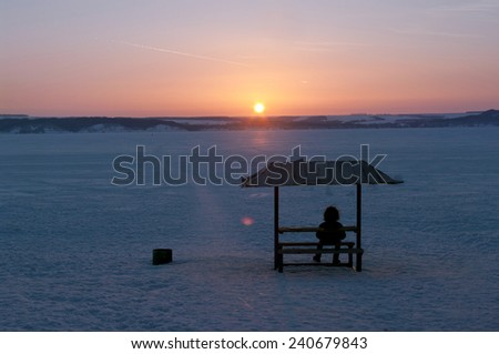 man sitting on bench watching sunset by frozen Volga river, Russia - stock photo