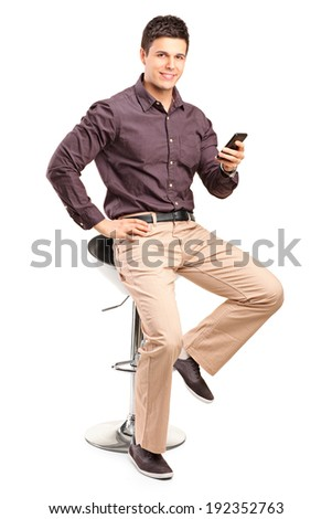 Man sitting on chair and holding cell phone isolated on white background - stock photo