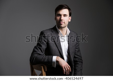 Man sitting on chair with dark wall in the background - stock photo