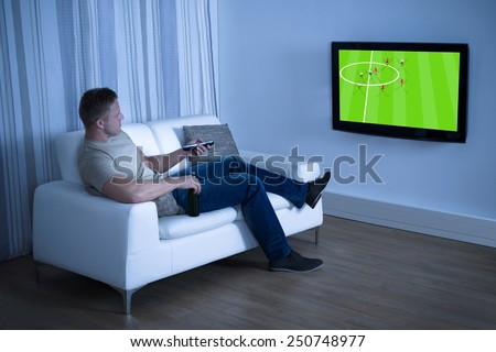Man Sitting On Couch Watching Soccer Game On Television At Home - stock photo