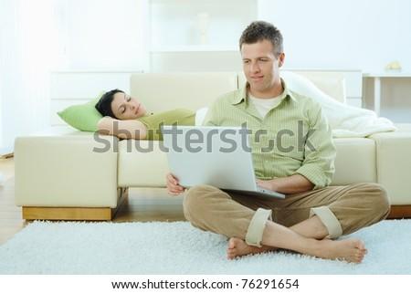 Man sitting on floor at home browsing internet on laptop computer, woman sleeping on sofa.? - stock photo