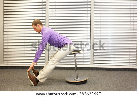 man sitting on pneumatic stool exercising touching his toes in office - stock photo