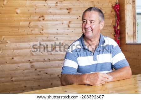 Man sitting on rustic table - stock photo