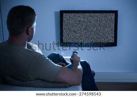 Man Sitting On Sofa In Front Of Television With No Signal - stock photo