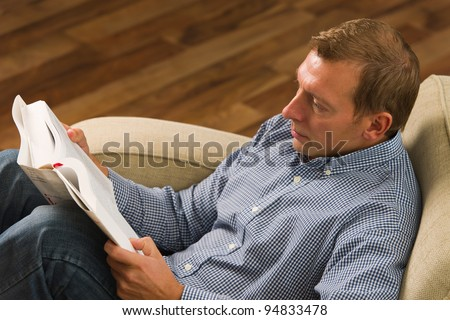 Man sitting on the armchair and reading the book. - stock photo