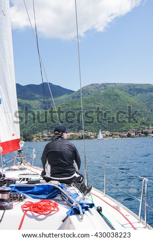 "Man sitting on the deck of the yacht. Tivat, Montenegro - 26 April, 2016. Regatta ""Russian stream"" in God-Katorskaya bay of the Adriatic Sea off the coast of Montenegro. - stock photo"