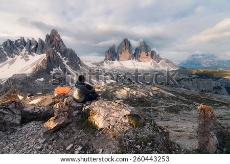 Man sitting on the mountain hill - stock photo