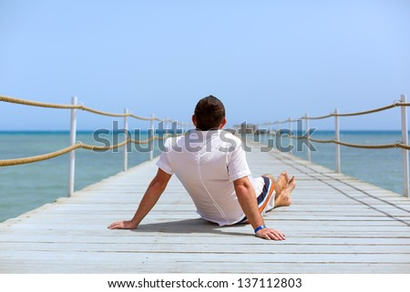 Man sitting  on the pier of Red Sea, Egypt - stock photo