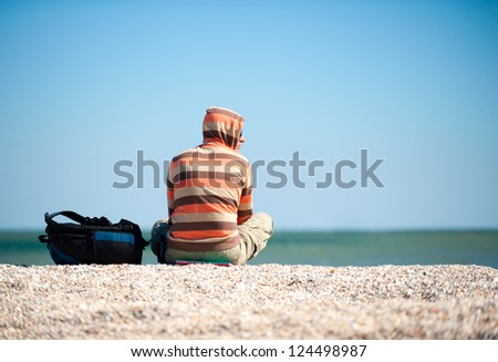 man sitting on the sand by the sea in the sun. Beside him is his backpack with things - stock photo