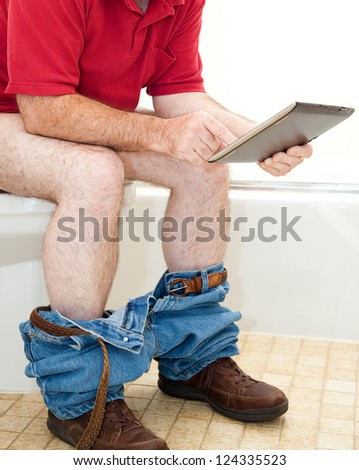 Man sitting on the toilet using his tablet PC. - stock photo