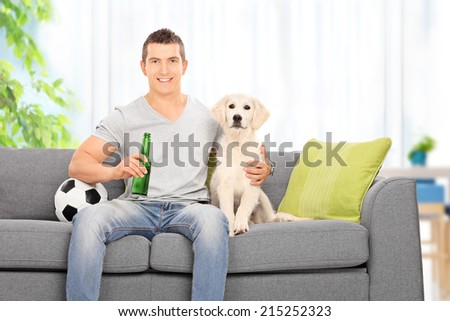 Man sitting with dog on couch and holding beer at home - stock photo