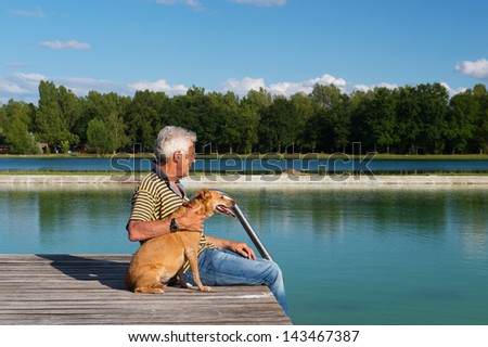 Man sitting with dog on pier at a lake - stock photo