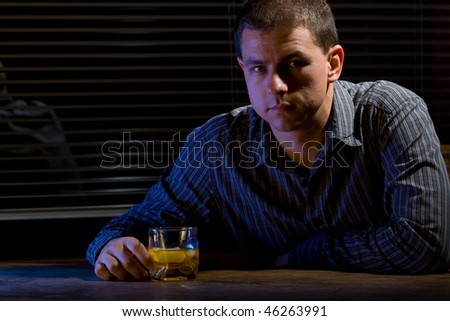 Man sitting with glass of whiskey at the office/home. - stock photo