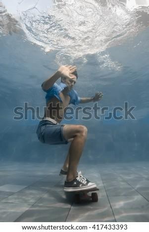 Man skateboarding underwater in the swimming pool - stock photo