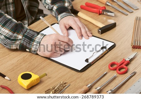 Man sketching a DIY project on a clipboard with work tools all around, hands close up, hobby and craft concept - stock photo