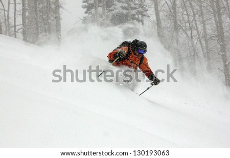 Man skiing deep powder snow during a blizzard in the Utah mountains, USA. - stock photo