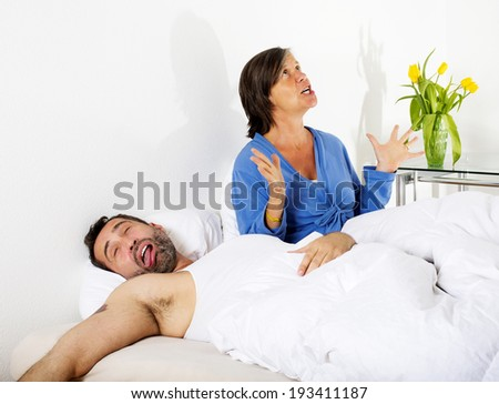 man sleeping and his wife is upset - stock photo