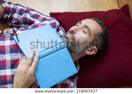 man sleeping and holding a book - stock photo