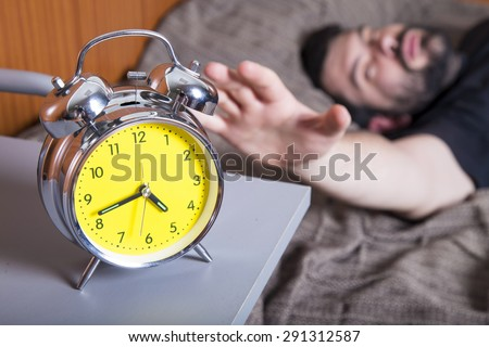Man sleeping in bed with an alarm - stock photo