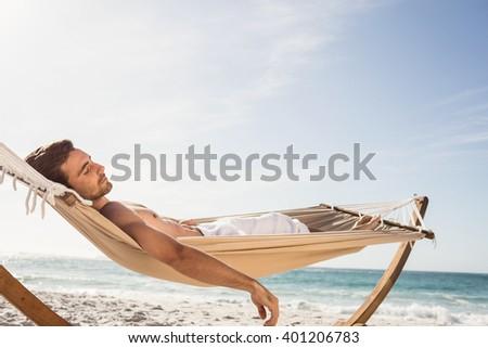 Man sleeping in hammock on the beach - stock photo