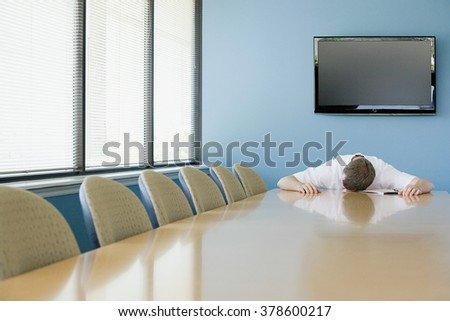 Man sleeping on conference table - stock photo
