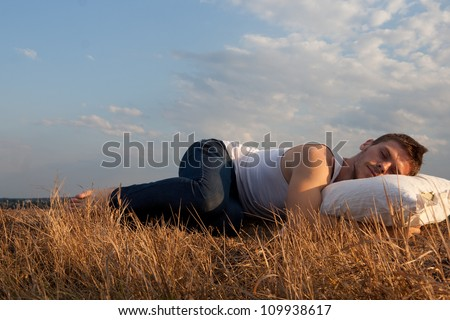 Man sleeping on field, rest concept. - stock photo