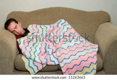 Man sleeping on the couch because he is feeling ill, or maybe he got in trouble with his wife - stock photo