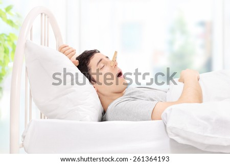Man sleeping with a clothespin on his nose at home - stock photo