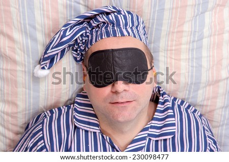 man sleeping with a mask on eyes - stock photo
