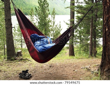 Man sleeps in a hammock and in a sleeping bag early in the morning - stock photo