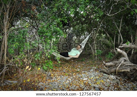 Man sleeps in Mexican hammock under trees in jungle - stock photo