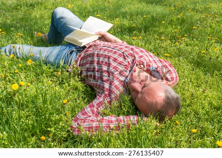 Man sleeps on a meadow with a book in hand - stock photo
