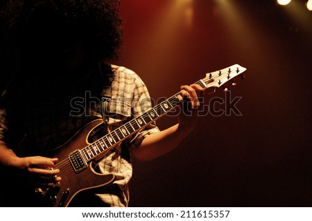 Man smashing his power cord on electric guitar - stock photo