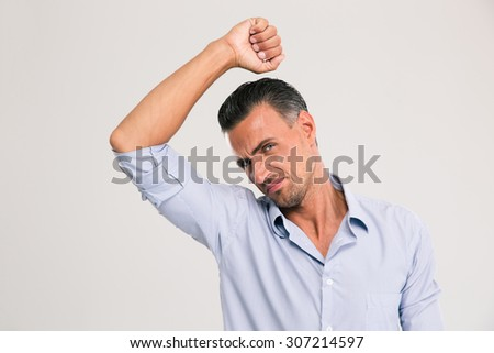 Man smelling sniffing his armpit something smells bad foul odor isolated on a white background - stock photo