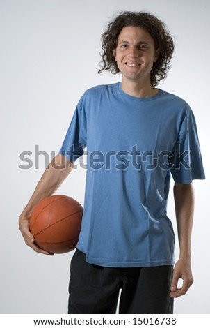 Man smiles as he holds a basketball. Vertically framed photograph. - stock photo