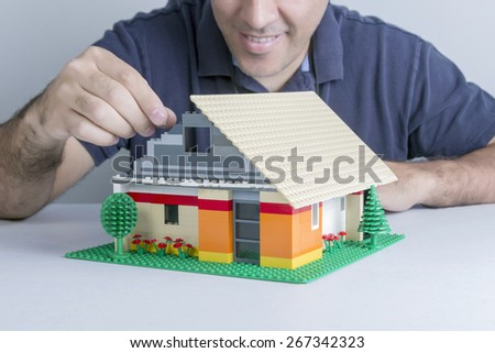 Man smiles while assembling a house with small parts in plastic - stock photo