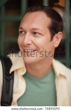 Man smiling and looking over his shoulder - stock photo