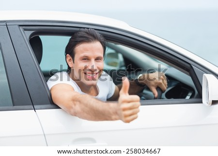 Man smiling and showing thumbs up in his car - stock photo