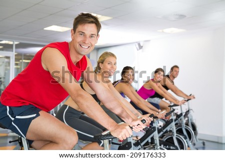 Man smiling at camera during spin class at the gym - stock photo