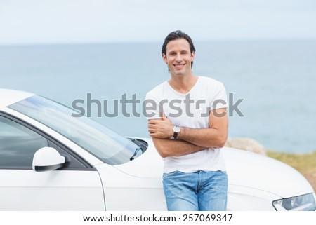Man smiling at camera outside his car - stock photo