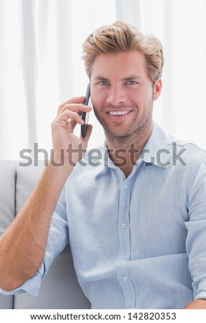 Man smiling while he is having a phone conversation on  his couch - stock photo