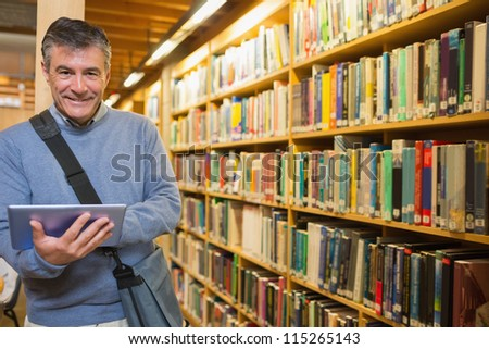 Man smiling while holding tablet pc in the library - stock photo