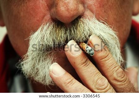 Man smoking a cigarette. Big cowboy style  mustaches - stock photo